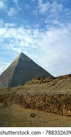 A wall running to the pyramid when the sky is blue