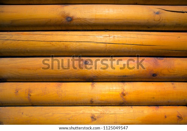 Wall of rural house made of light logs with cracks and knots, may be used as background or texture
