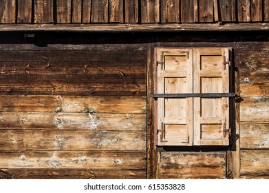 Wall of a rustic, wooden house with a window on the right