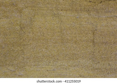 Wall of sandstone with homogeneous and random distribution of sand grains of different colors and stone layers of different colors. Close up architecture photography. Creative wallpaper photography.