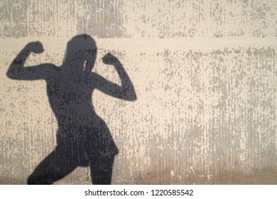 Wall shade of woman's silhouette showing her biceps. Silhouette on the decayed wall in sunlight.
