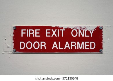 Wall signage that says, FIRE EXIT ONLY DOOR ALARMED.