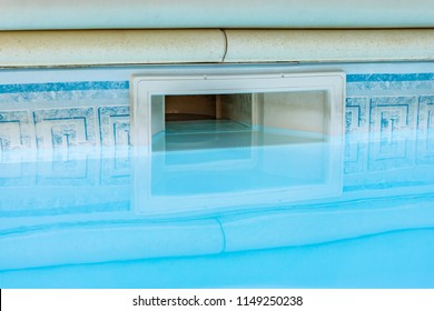 Wall skimmer equipment filtration swimming pool system with reflection on blue water pool.