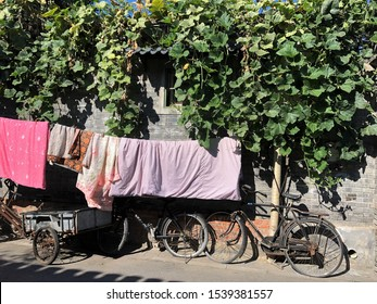 Wall in small street. Clothes, blankets are hung and bicycles are parked along the wall. Everyday life of local people in Beijing, China.