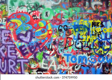 a wall sprayed with colorful banners and graffiti