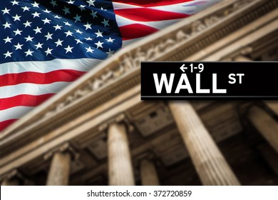 Wall Street sign with American flag on the background.