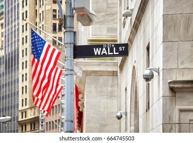 Wall Street sign with American flag in distance, shallow depth of field, New York City, USA.