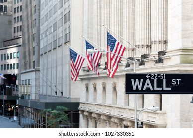 Wall Street sign with american flags and New York Stock Exchange in New York City.