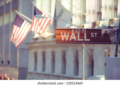 Wall Street sign with American flags and New York stock exchange in the background.
