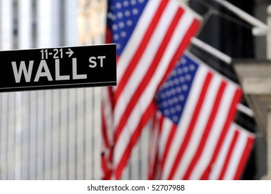 """Wall Street"" sign in focus, with American flags blurred in the background, shot in the heart of the business world in Manhattan."