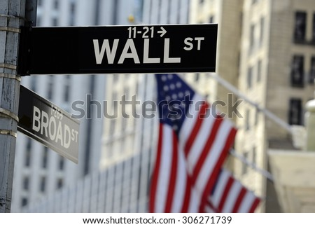 Wall street sign with focus on sign, blurred American flag background