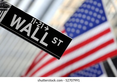 """Wall Street"" sign in focus, pointing down, with American flags blurred in the background, shot in the heart of the business world in Manhattan."