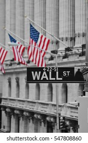 A wall street sign in front of the American flags