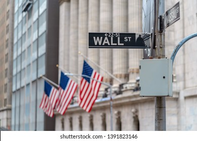 """Wall Street """"WALL ST"""" sign over American national flags in front of NYSE stock market exchange building background. The New York Stock Exchange locate in economy district,Business and landmark concept"""
