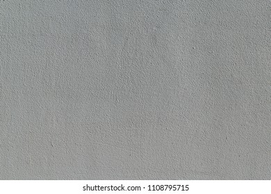The wall surface is lined with plaster and painted with gray paint. The surface is rough with small pimples and hollows, strips. The wall is homogeneous and rough. Background, backdrop.
