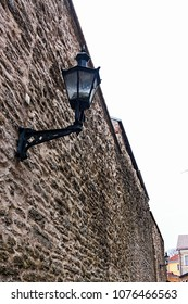 The wall surrounding the medieval old town of Tallinn is lit with lanterns like this. You can see some of the restorated houses in the background.