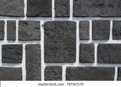 Wall texture made of black blocks of basalt with gaps painted in white. A typical construction style which is widely used at many places of Azores, Portugal.