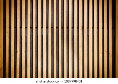 Wall of thin wooden slats. Vertical parallel plates. Empty background with vignette.