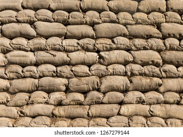 Wall of tightly packed sandbags in an alternating brick bond