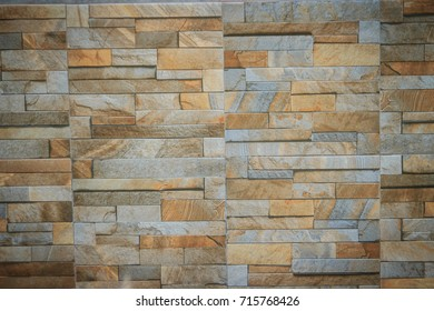 Wall tiles patterned like natural split stone background. Simulated yellow natural stone facade, wall tiles texture.
