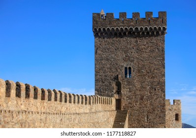 The wall and the tower of the ancient fortress against the background of the blue sky in the Crimea