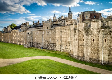 The wall of the Tower of London, and the green lawn outside of it on a summer sunny day. The historic castle is located on the north bank of the Thames and was built by William the Conqueror in 1078