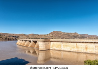 Wall of the Vanderkloof Dam in the Orange River. The road to the Vanderkloof town in the Northern Cape Province is visible on the hills in the back