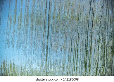 Wall of water. A beautiful view of a blue sky and green trees through the falling water cascade.