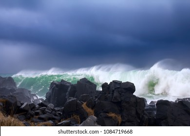 Wall of water like tsunami - turbulent waves of Pacific ocean more than 8 meters (heavy) and rugged beauty of basalt rocks (reef, cay cavity, shoal head)