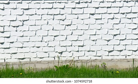 Wall, white brick wall and green grass with flowers