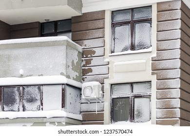 Wall with windows of modern high-rise apartment building covered with snow and frost after heavy windy snowstorm Snowfall and blizzard aftermath in winter. Cold snowy weather forecast