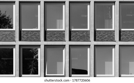 A wall of windows of an office building with refelctions in the windows.