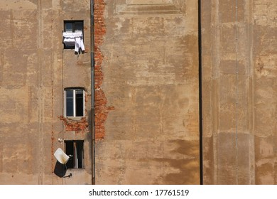 Wall with windows on which is laundry and satellite