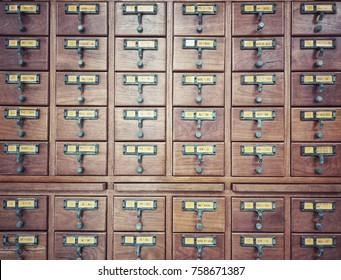 Wall of wooden boxes for index cards in library.