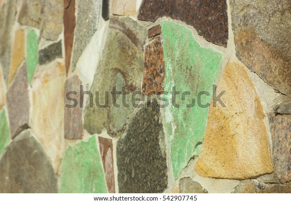 Wall of yellow with accents of blue and green natural stone close - up