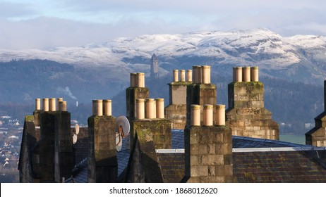 Wallace Monument in between chimneys of roofs of Stirling's houses and hills covered in first snow in the background on a brisk morning