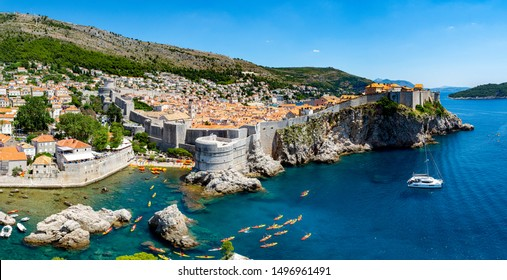 The walled city of Dubrovnik, Croatia taken from Fort Lovrijenac. The turquoise clear water of the Adriatic surrounds the ancient walled city of Dubrovnik, kayaks and a sailing boat provides scale.