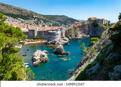 The walled city of Dubrovnik, Croatia taken from Fort Lovrijenac. The turquoise clear water of the Adriatic surrounds the ancient walled city, kayaks and a sailing boat provides scale.