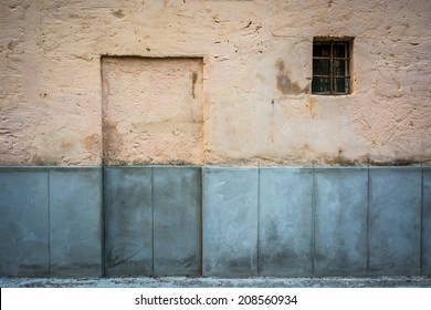 Walled door and grilled window on the facade of an old house