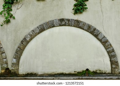 A walled door with a stone arch e against the background of an old beige plastered wall, photo frame, text place