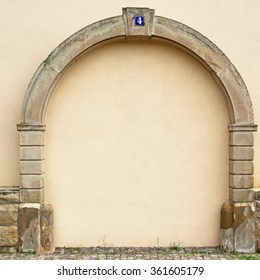 The walled-up door with stone arch with metal rusty blue table with white number four on the ancient beige plastered walls background, photo frame, place for text