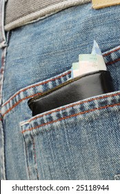 Wallet in back pocket of jeans with money sticking out