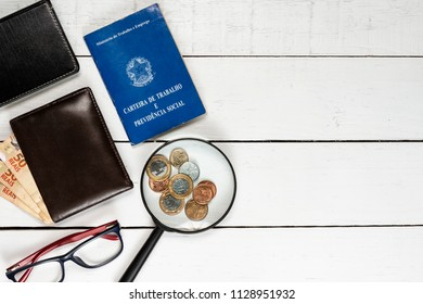 Wallet with Brazilian money notes, glasses,  glasses, leather notepad, Brazilian coins and work permit on white background pinus