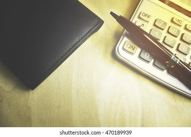 wallet with a calculator and a pen on the desktop
