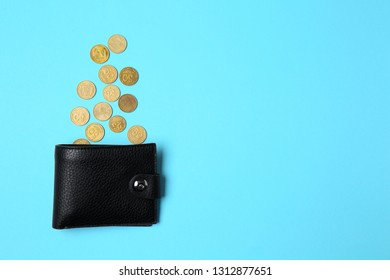 Wallet and coins on color background