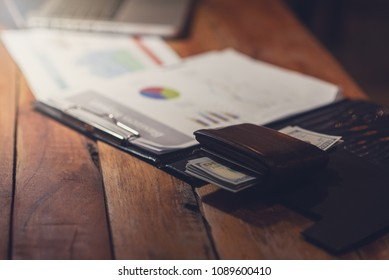 Wallet with dollar and business documents on the table.