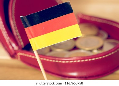 A wallet, flag of Germany and Euro coins