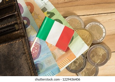 A wallet, flag of Italy and euro bills and coins