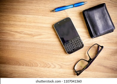 Wallet, glass, smartphone and pen left on a desk