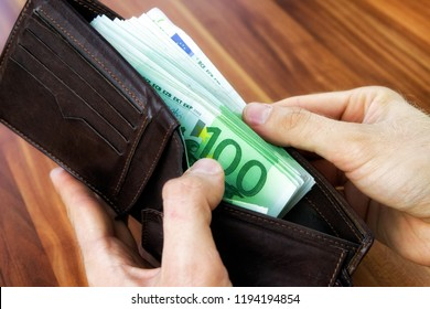 Wallet in hands full of  100 euro cash money banknotes. Close up view